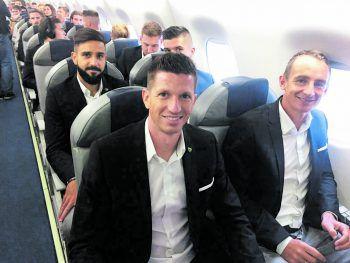 """<p class=""""caption"""">Mit breiter Brust im Flugzeug: Lienhart, Aigner, Galvao und der Rest des Teams.</p>"""