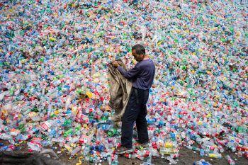 <p>Beijing. Nachhaltig: Ein Mann in China sortiert recyclebare Plastikflaschen aus einem riesigen Müllberg aus. </p>