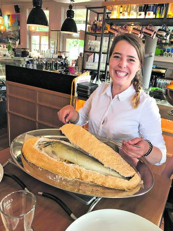 Kellnerin Jana zerlegt den Zander in Salzkruste direkt vor den Gästen am Tisch. Fotos: W&W