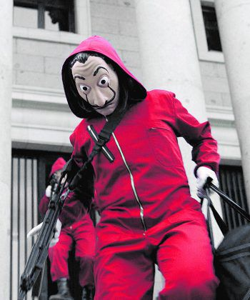 Mit roten Overalls und Dali-Masken ziehen sie den Überfall durch.