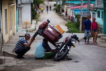 <p>Santa Clara. Erfinderisch: Zwei Männer reparieren in Kuba ein Motorrad auf ziemlich ungewöhnliche Art und Weise. Fotos: AP, AFP, APA, Reuters</p>