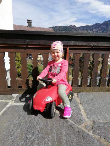 """<p class=""""caption"""">Verena (2,5) auf Omas Terrasse beim Bobby-Car-fahren.</p>"""