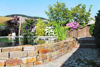 Ein Schwimmteich ist das absolute Highlight in jedem Traumgarten und wirkt durch die Gestaltung mit Natursteinen besonders edel.