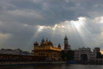 <p>Amritsar. Malerisch: Die Sonne, die durch die Wolkendecke bricht, taucht den Goldenen Tempel in ein magisches Licht.</p>