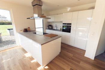 """<p class=""""caption"""">Die Küche mit Kochinsel und direktem Zugang zur Terrasse bietet viel Platz um der Leidenschaft fürs Kochen gerecht zu werden.</p>"""