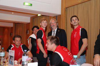 """<p class=""""caption"""">Heinrich Olsen (3. v.l.) unter seinen begeisterten Sportlern.</p>"""