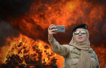 <p>Peshawar. Selfie: Eine pakistanische Polizistin schießt ein Erinnerungsfoto, während Drogen verbrannt werden.</p>