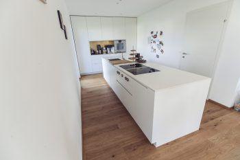 """Der ganze Stolz der Familie: die Küche, die bewusst ganz in weiß gehalten wurde – so wirkt sie wie aus """"einem Guss""""."""