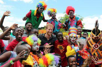 <p>Lusaka (Sambia). Farbenfroh: Prinz Harry posiert für ein Foto inmitten einer bunten Schar von Zirkusleuten.</p>