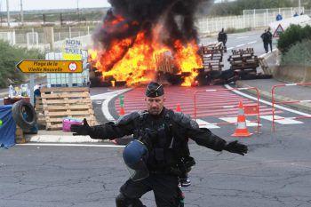 <p>Port La Nouvelle. Feurig: Ein Gendarm vor einer von Demonstranten anlässlich der hohen Spritpreise errichteten Barrikade.</p>