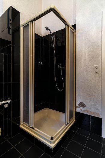 Vorher. Kleine, rutschige, sehr pflegeintensive Dusche mit Absatz – Stolperfalle!