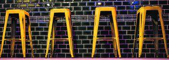 """<p class=""""caption"""">Stylisch: Die Bar in edler grüner Fliesenoptik im Kontrast zu den gelben Metallhockern.</p>"""