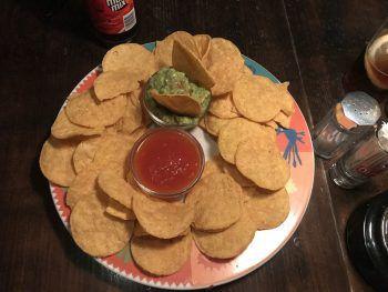 "<p class=""caption"">Tortillachips mit Guacamole und Salsa.</p>"