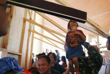 """<p>               Manila. Gläubig: Ein Kind küsst das Kreuz beim Fest des """"Schwarzen Nazarenes"""".             </p>"""