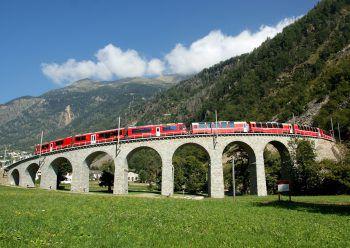 Die Bernina-Express auf dem bekannten Kreisviadukt bei Brusio. Eine Fahrt von den Gletschern zu den Palmen.
