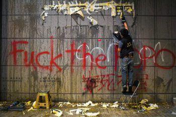 <p>Hongkong. Beschädigt: Ein Polizist säubert eine Wand, die im Zuge der Proteste beschmiert wurde.</p>