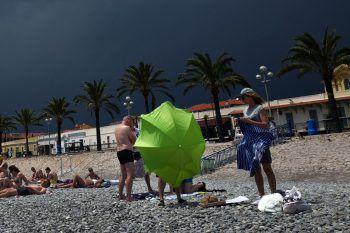 <p>Nizza. Stürmisch: Badegäste machen sich daran, den Strand zu verlassen, während im Hintergrund ein Gewitter aufzieht.</p>