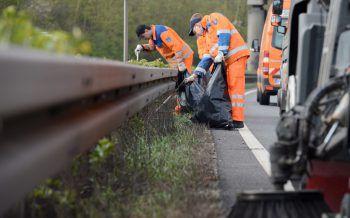 Männer sammeln Müll vom Rand der Autobahn. Foto: dpa