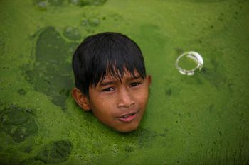 <p>Nepal. Bedrückend: Ein Junge schwimmt in einem von Müll und Algen bedeckten Teich.</p>
