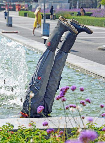 """<p>Karlsruhe. Erfrischend: Die Kunstinstallation """"Spring-Brunnen"""" stellt einen Bauarbeiter dar, der sich im Brunnen abkühlt.</p>"""