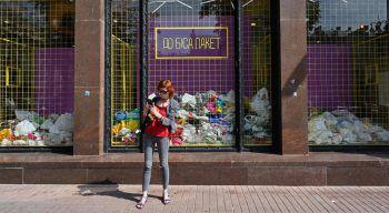 """<p>Kiev. Demonstrativ: Eine Frau steht vor einem Container mit Plastiksäcken, auf dem steht: """"Zur Hölle mit dem Müll"""".</p>"""