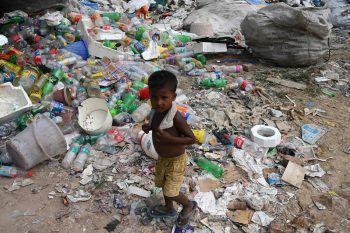 <p>Neu Delhi. Erschütternd: Ein kleiner Junge läuft über gewaltige Berge von Plastikabfällen. Fotos: APA, AFP</p>