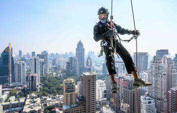 <p>Bangkok. Schwindelfrei: Ein Arbeiter bringt hoch über den Dächern der thailändischen Hauptstadt Feiertagsdekoration an.</p>