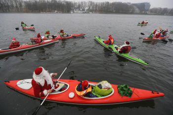 """<p>Minsk. Auffällig: Menschen in Weihnachtsmann-Kostümen paddeln beim """"Santa Rennen"""" auf dem Komsomolskoye See in Weißrussland.</p>"""
