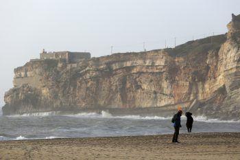 <p>Nazara. Verspielt: Ein Mann spielt an der Küste Portugals Frisbee mit seinem Hund.</p>