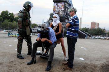 <p>Santiago. Angespannt: Ein Polizist in voller Kampfmontur und mit Schlagstock stellt sich neben eine vermummte Demonstrantin, die auf dem Plaza Italia anderen Demonstranten Massagen anbietet. Ob der Polizist ebenfalls eine Massage erhielt, ist nicht bekannt.</p>
