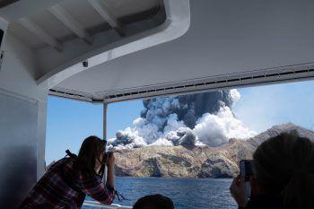 Touristen fotografieren die Eruption.