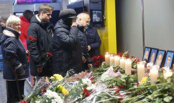 Angehörige legen am Flughafen in Kiew Blumen für die Opfer nieder und trauern. Foto: AP