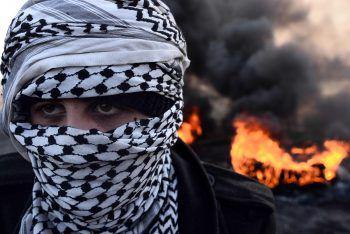 <p>Najaf. Vermummt: Ein irakischer Demonstrant protestiert vor brennenden Barrikaden gegen die Regierung.Fotos: APA, AFP, Reuters</p>
