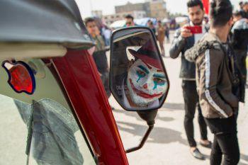 <p>Bagdad. Angemalt: Ein irakischer Demonstrant, der als Joker verkleidet ist, schaut in den Rückspiegel eines Tuk-Tuk.</p>
