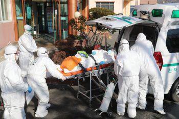 <p>Cheongdo. Erkrankt: Südkoreanische Rettungskräfte verlegen einen an Covid-19 erkrankten Patienten.</p>