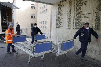 Krankenhauspersonal im norditalienischen Codogno schieben neue Betten in ein Spital. Foto: AP