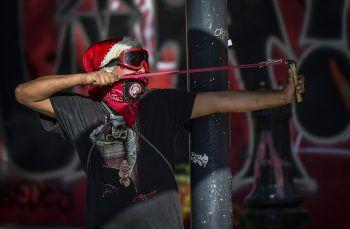 <p>Santiago. Extrem: Ein Demonstrant feuert während einer Demo gegen Präsident Pinera mit einer Steinschleuder Geschosse auf Polizisten.</p>