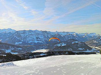 """<p class=""""caption"""">Wunderschöner Paragleittag: Susanne inmitten verschneiter Berge.</p>"""