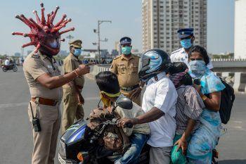<p>Chennai. Mahnend: In der indischen Stadt weist dieser Polizist mit Coronavirus-Spezialhelm auf die Vorsichtsmaßnahmen hin.</p>