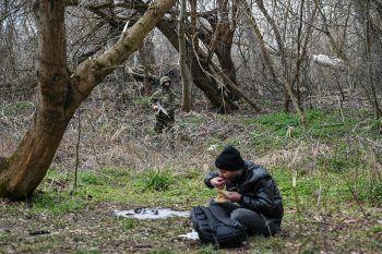 <p>Pazarkule. Dramatisch: Ein Flüchtender isst, während im Hintergrund ein griechischer Soldat die Grenze zur Türkei bewacht.</p>