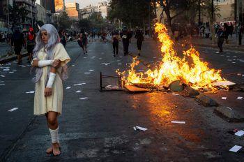 <p>Santiago. Kritisch: Eine Demonstrantin steht vor einer brennenden Straßenbarrikade bei Protesten gegen Chiles Präsident Sebastian Pineras.</p>