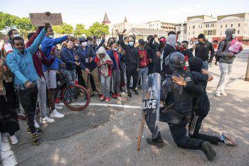 """<p class=""""caption"""">Auch in Minneapolis kniet ein Polizist mit einem Demonstranten nieder. Fotos: AP, APA</p>"""