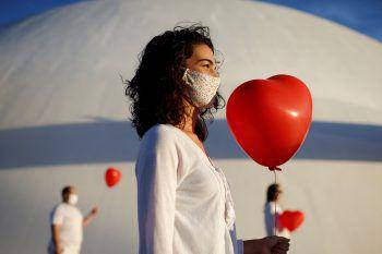 <p>Brasilia. Performance: Künstler setzen ein Zeichen mit roten Herz-Luftballons und erweisen so den Menschen die Ehre, welche durch den Coronavirus verstorben sind.</p>