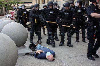 """<p>Buffalo. Erschreckend: """"Riot Police"""" marschiert an Martin Gugino (75) vorbei, der bei einer Demo von einem Polizisten niedergestoßen wurde und mit einer Kopfverletzung bewusstlos am Boden liegt.</p>"""