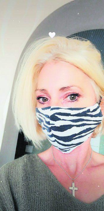 "<p class=""caption"">Daniela trägt eine Zebra-Maske.</p>"