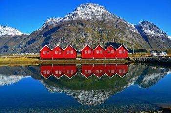 Einige Bootshäuschen im norwegischen Sunndalsøra spiegeln sich im klaren Wasser. Fotos: handout/Johannes Rusch