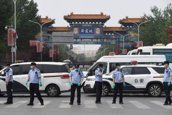 <p>Peking. Maskiert: Chinesische Polizisten riegeln nach einem neuen Ausbruch des Corona-Virus einen Markt ab.</p>