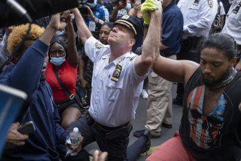 """<p class=""""caption"""">Polizisten beim """"Kneel-In"""": Terence Monahan, Polizeichef von New York, kniet mit Demonstranten nieder und umarmt sie.</p>"""