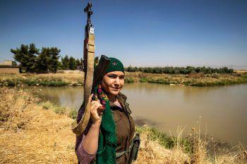 Qamishli. Bewaffnet: Eine kurdische Freiwillige bewacht mit einem Sturmgewehr ein Weizenfeld im Nordosten Syriens. Fotos: AFP, APA, dpa