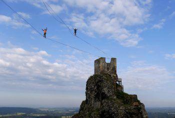 <p>Turnov. Hoch: Zwei Menschen laufen auf einem Seil bei einem Event auf der Burg Trosky in Tschechien.</p>